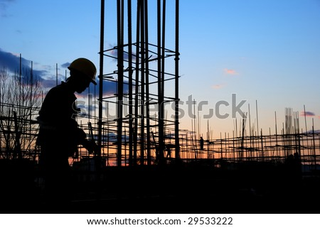Builder Silhouette at Construction Site at Dusk - stock photo