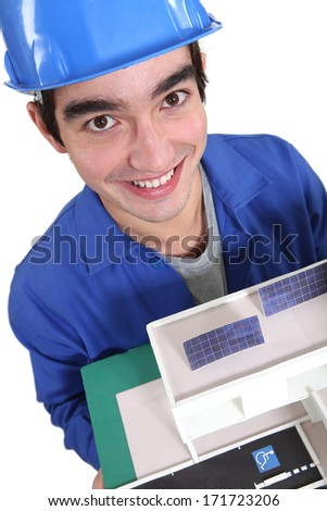 Builder stood with model house - stock photo