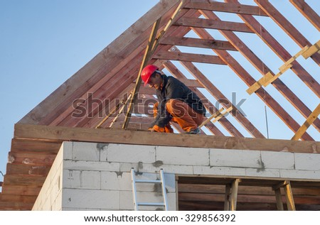 Builder trying to board attic floor joists - stock photo