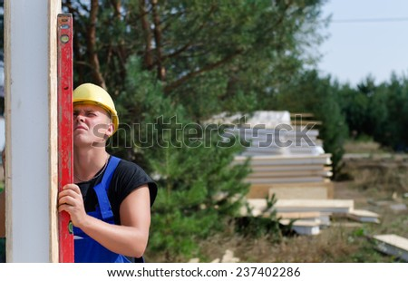 Builder using a builders level against an upright wooden insulated wall panel to ensure it is vertical - stock photo