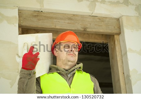Builder with a concrete block on shoulder at new building - stock photo