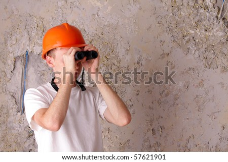 builder with binoculars at the background of the gray plastered walls - stock photo