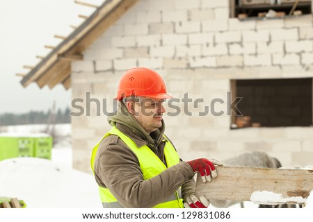 Builder with board at the hands near the construction works - stock photo