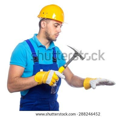 Builder with protective gloves holding hammer and knocking something, isolated on white