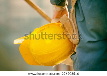 builder with yellow hardhat and gloves - stock photo