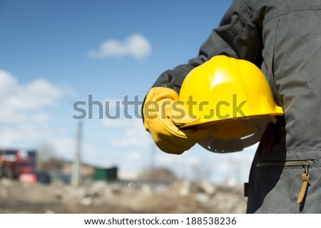 builder with yellow hardhat and gloves, selective focus - stock photo