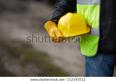 builder with yellow helmet and working gloves on building site - stock photo