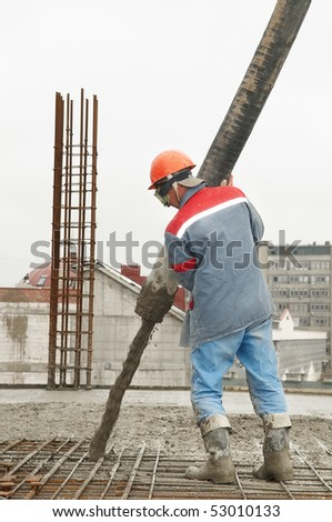 builder worker aiming pump tube during concrete pouring process - stock photo