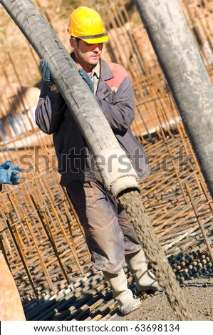builder worker aiming pump tube during concrete pouring process at construction site - stock photo