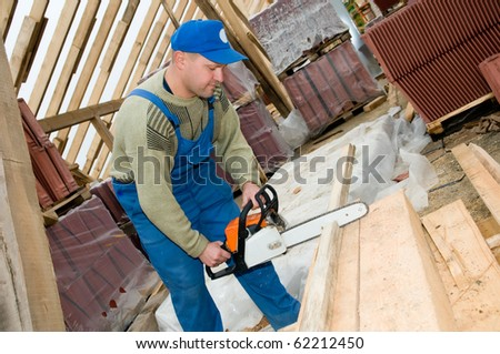 builder worker at roofing works cutting wood timber with po?table saw - stock photo