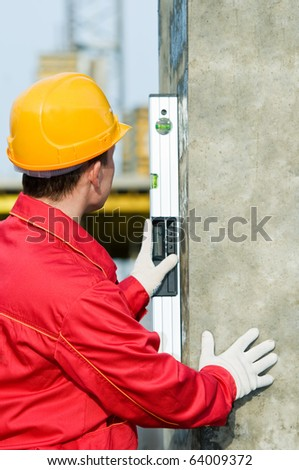 builder worker checking vertical with digital level tool at construction site - stock photo