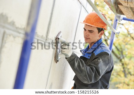 builder worker facade building with sandpaper - stock photo