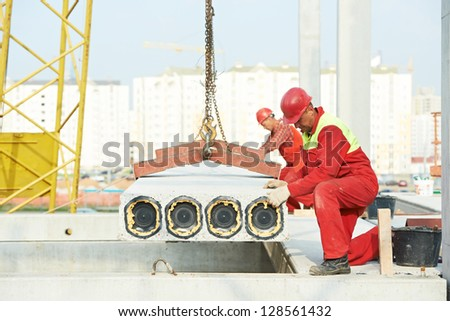 builder worker in safety protective equipment installing concrete floor slab panel at building construction site - stock photo