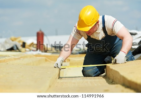 builder worker inspecting insulation material by measuring tape at roof - stock photo