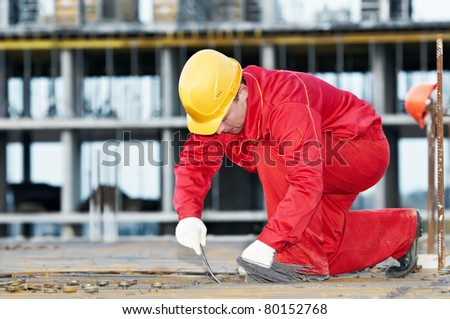 builder worker knitting metal rods bars into framework reinforcement for concrete pouring at construction site - stock photo