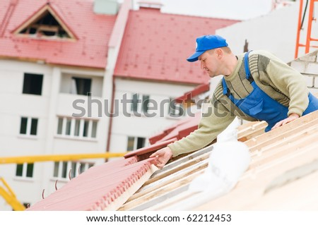 builder worker laborer at roofing tiling works - stock photo