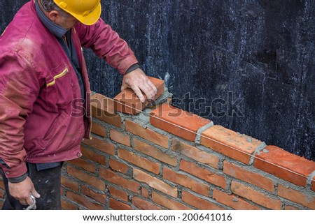 Builder worker laying solid clay brick, bricklaying  - stock photo
