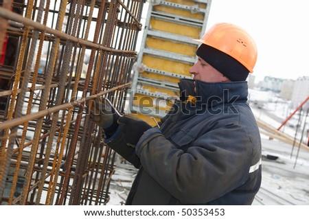 Builder worker making reinforcement metal framework lattice for concrete pouring - stock photo