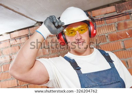 Builder worker man portrait in hardhat with glasses and earmuffs or ear defenders at construction site - stock photo