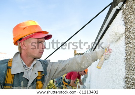 builder worker painting facade of building house with roller - stock photo