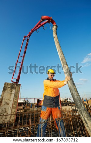 builder worker standing near trailer-mounted boom concrete pump on metal rods reinforcement of concrete casting formwork - stock photo