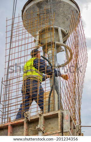Builder worker using concrete funnel for aiming and placing concrete. - stock photo