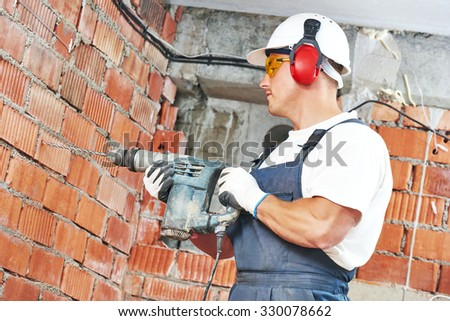 Builder worker with pneumatic hammer drill perforator equipment making hole in wall at construction site - stock photo