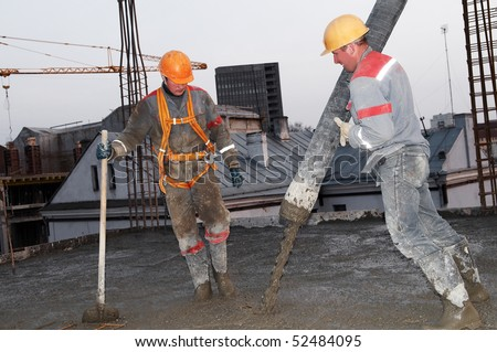builder workers aiming pump tube during concrete pouring process - stock photo