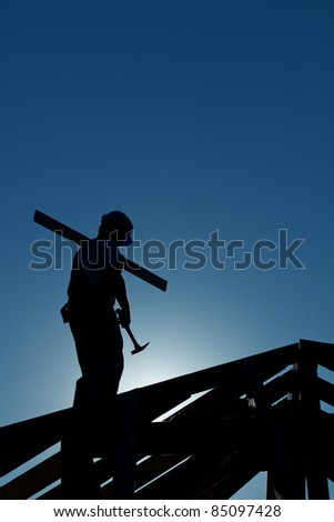 Builder working late on top of building holding hammer - in strong back light - stock photo