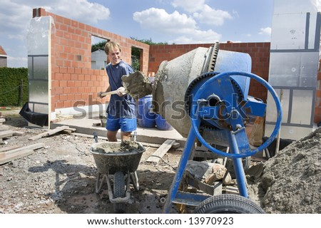 builder working with a concrete mixer. Spade in hand. - stock photo