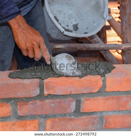 Builders are laying cement mixed with water, sand and bricks will be laid in a row, alternating with mortar to help the adhesion and strength of a brick wall using a trowel to work. - stock photo