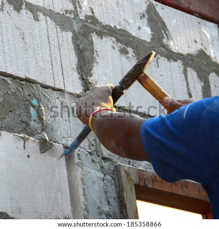Builders are using a chisel and hammer penetrate brick wall to make a hole for the PVC pipe for electrical conduit trust inside.chisel hammer worker extract mortar brick brick wall wall drill.  - stock photo