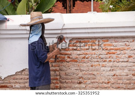 Builders are using a chisel and hammer to punch a brick wall, cement plaster falls off. - stock photo