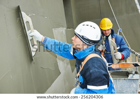 builders at facade plastering work during industrial building with putty knife float - stock photo