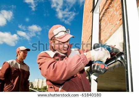 Builders laborer in work wear screwing a screw with screwdriver machine - stock photo