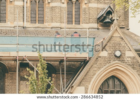 Builders repairing roof of a church standing on scaffolding, church in background - stock photo