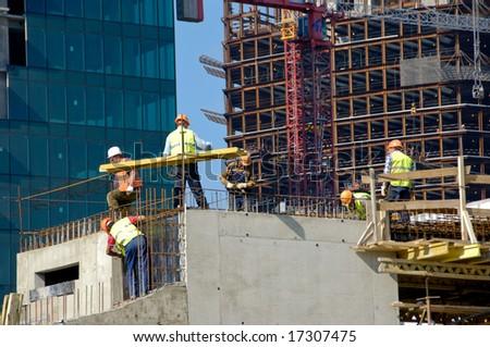 Builders work on skyscraper construction - stock photo