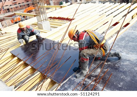 builders working in protective wear, helmet and equipment - stock photo