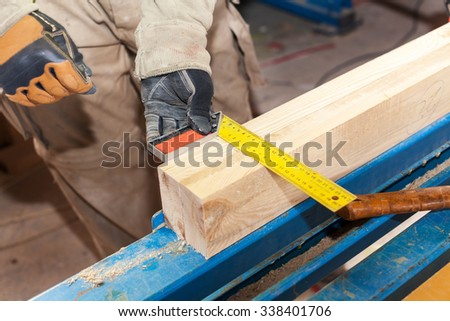 Building a wall for frame house. Worker make marks for cutting timber