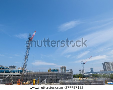 building and cranes under construction against blue sky