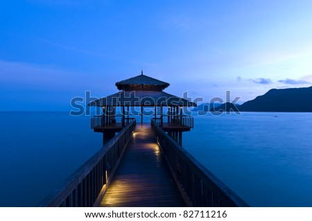 Building at the end of a jetty during twilight light illuminated - stock photo