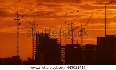 building background. Hoisting crane and the contours of house on sunset view. Construction site at orange or yellow cloudy sky. urban backdrop