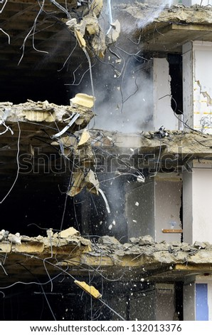 Building collapsing or being demolished with debris falling down - stock photo
