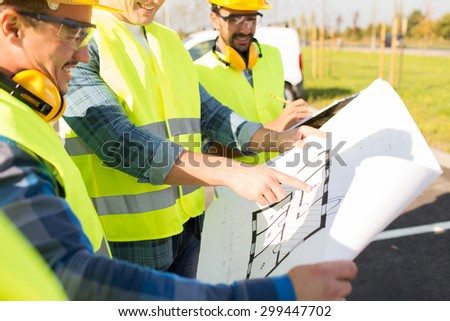 building, construction, development, teamwork and people concept - close up of builders high visible vests with blueprint at building site - stock photo