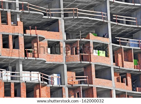 Building construction site from concrete and brick with railing - stock photo