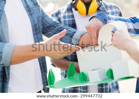 building, construction, teamwork and people concept - close up of builders hands with paper house model or layout outdoors - stock photo