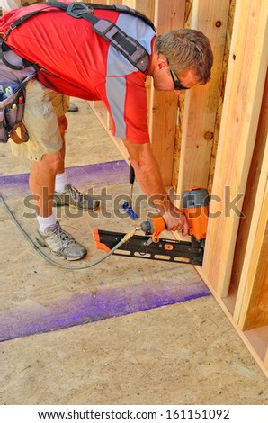 Building contractor worker using a air nail gun to attach the wall for the second floor on a new home construction project - stock photo
