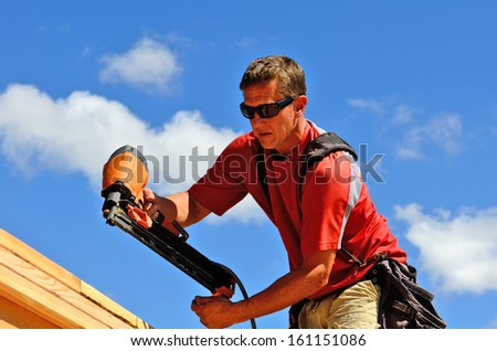 Building contractor worker with a air nail gun  nailer working on the corner of the top plate of the first floor walls on a new home construction project - stock photo