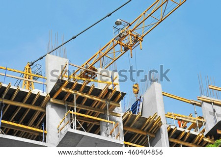 Building crane and building under construction against blue sky