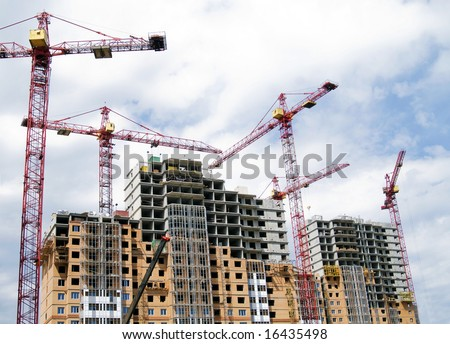 Building crane and building under construction against cloudy sky - stock photo